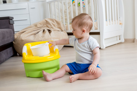 chamber pot: Adorable 10 months old baby boy learning how to use chamber pot