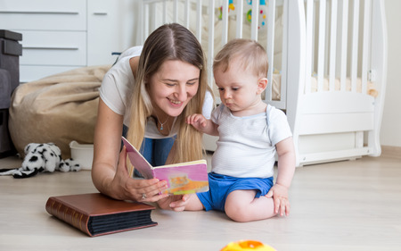Portrait of beautiful young mother reading book to her baby boy