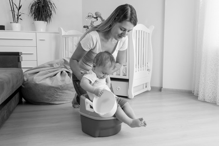 chamber pot: Black and white image of mother sitting her baby on chamber pot Stock Photo