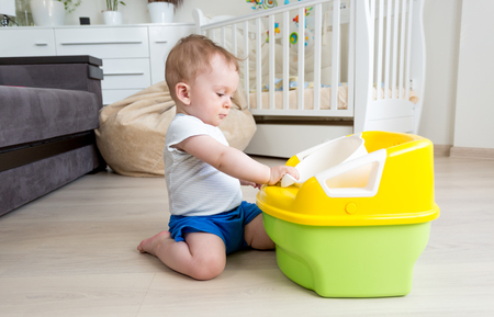 chamber pot: Adorable baby boy sitting on floor and looking at chamber pot