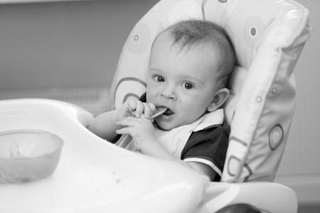 9 months old: Black and white portrait of 9 months old baby boy sitting in highchair and holding spoon Stock Photo