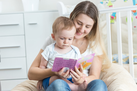 9 months old: Portrait of beautiful smiling mother reading book to her 9 months old baby boy