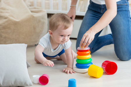 tower house: Adorable baby boy crawling on floor and assembling toy tower with mother