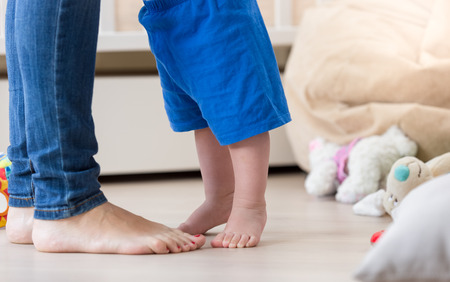 baby's feet: Closeup photo of babys feet standing in front of mothers feet on floor at living room