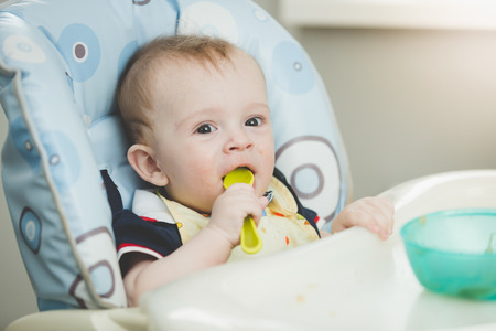 smudgy: Portrait of adorable baby boy eating from spoon in highchair on kitchen Stock Photo