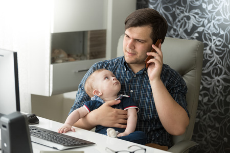 Portrait of father talking by phone and taking care of his baby