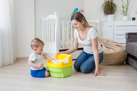 Young smiling mother sitting on floor at living room and teaching her 10 months old baby boy how to use chamber pot