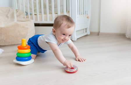 9 months old: Adorable 9 months old baby boy playing with toy tower at living room