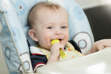 playing with spoon: Portrait of beautiful 9 month baby boy playing with spoon while eating Stock Photo