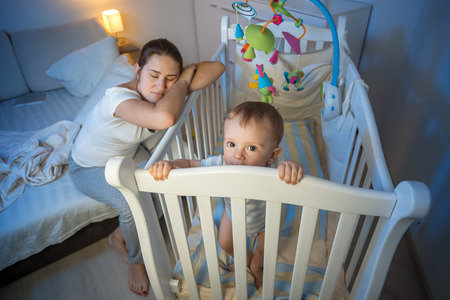 Young tired mother got asleep next to baby's crib