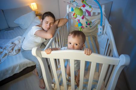 Mama zmęczona matka zasnęła obok łóżeczka dziecka