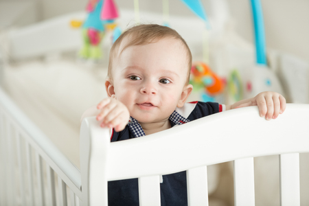 Portrait of 9 month old boy teething and posing in white cradle