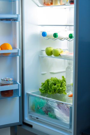 refrigerator kitchen: Open refrigerator full of food on kitchen at night Stock Photo
