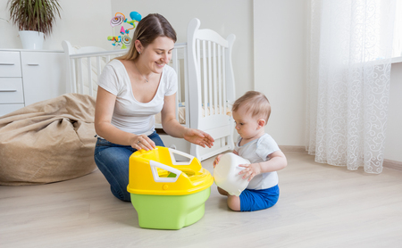 chamber pot: lYoung oving mother teaching her baby boy how to use chamber pot