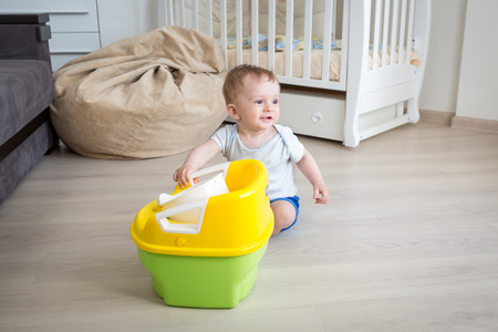 chamber pot: Adorable baby boy playing with chamber pot on floor at living room