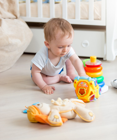 Cute 9 months old baby boy playing with colorful toys on floor at living room