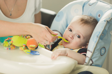 9 months old: Toned portrait of mother feeding her 9 months old son from spoon Stock Photo