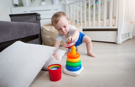 9 months old: 9 months old baby boy crawling on floor at living room and reaching for toy tower