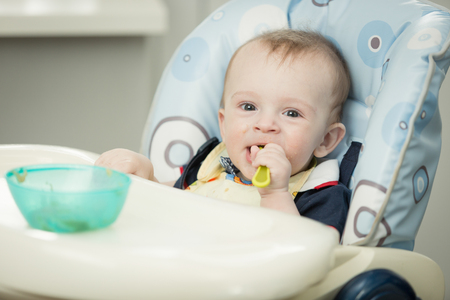 9 months old: Toned portrait of adorable 9 months old boy eating in highchair at kitchen