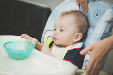 9 months old: Portrait of 9 months old baby boy sitting in highchair and reaching for dish