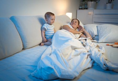 sleepless: Sleepless baby boy waking up mother sleeping in bed