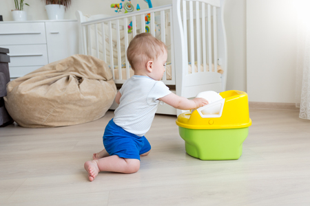 chamber pot: 10 months old baby boy trying to sit on chamber pot at bedroom