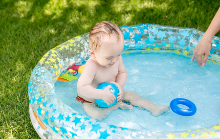 Cute 9 months old baby boy playing with ball in pool at garden