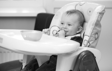 9 months old: Black and white portrait of 9 months old baby sitting in highchair and playing with food Stock Photo