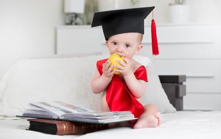 Portret van schattige babyjongen in graduatie GLB zit in van van boeken en bijtende appel. Concept wijzer baby groeien
