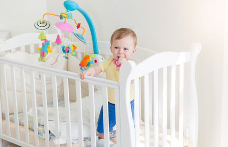 wail: Sad 10 months old baby boy crying and holding to the side of crib Stock Photo