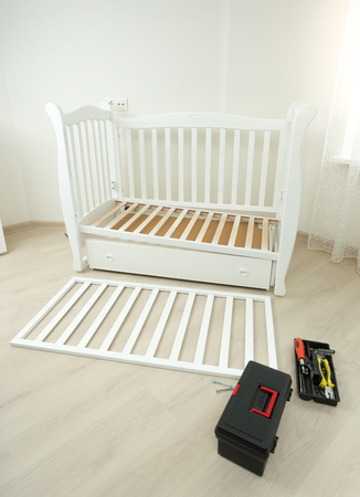 Tools box lying on floor next to disassembled wooden baby bed