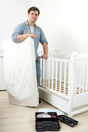 fixate: Young smiling man standing with mattress at disassembled babys cot Stock Photo
