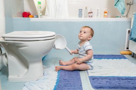 Adorable baby boy sitting on floor at bathroom