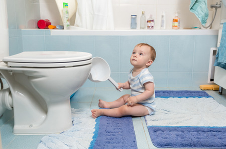 Adorable baby boy sitting on floor at bathroom