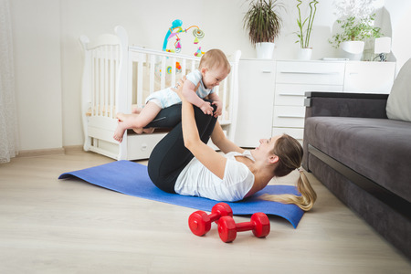Beautiful young mother holding baby and practicing yoga