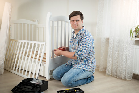 assembler: Happy young man assembling white wooden crib in nursery