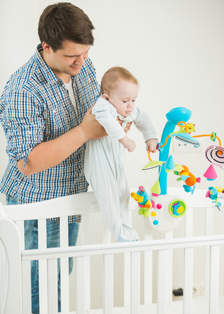 9 months old: Portrait of young man taking his 9 months old baby son out of cot Stock Photo