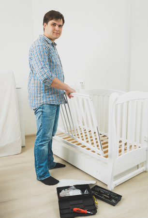 cot: Young handsome man in jeans and shirt assembling babys cot