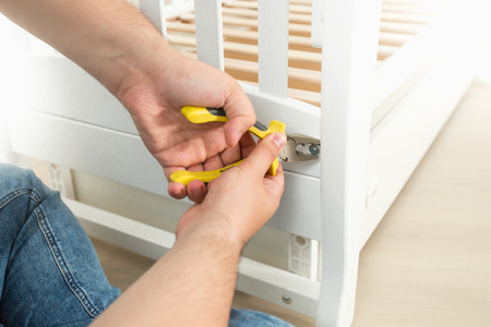 Closeup photo of man disassembling white wooden bed Stock Photo
