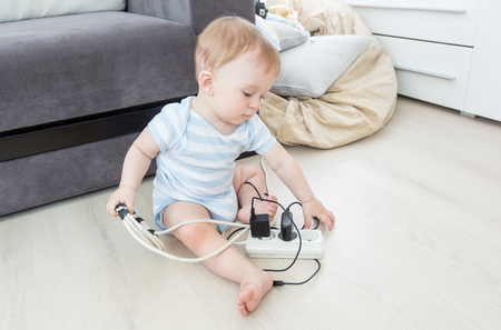 Adorable baby boy playing with electrical extension and wires on floor Фото со стока