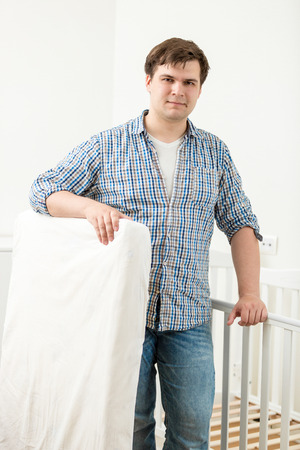 Portrait of young handsome man  posing at babys cot with new mattress