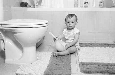 tidiness: Black and white image of adorable baby boy sitting on floor at bathroom Stock Photo