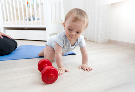 levantar peso: Cute baby boy crawling on floor and playing with dumbbells