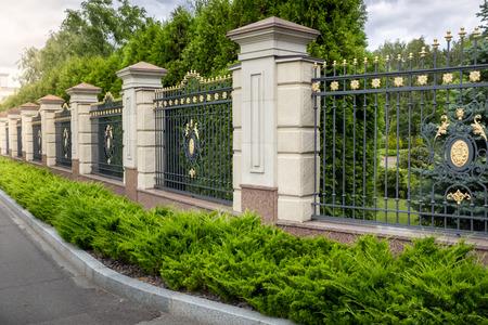 Piękne kute ogrodzenia malowane złotem przy wejściu do luksusowej willi