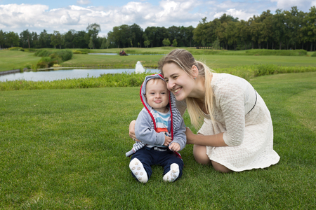 Adorable 9 months old baby boy sitting on grass at park with his beautiful mother
