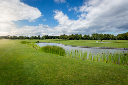 Beautiful view of golf course with water hindrance at sunny day Stock Photo