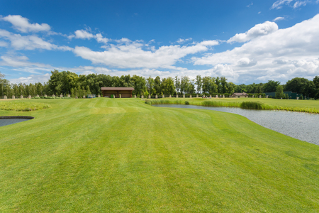 Beautiful golf course with perfect green grass and water hindrance at bright sunny day