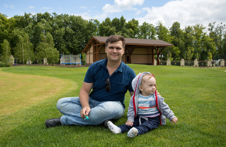 9 months old: Young father with his 9 months old baby boy relaxing on green grass at park