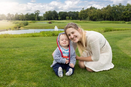 9 months old: Portrait of beautiful young mother and cheerful 9 months old baby boy relaxing on grass at park