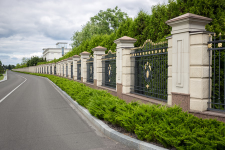 Beautiful long stone fence with forged metal gates painted with gold Stock Photo